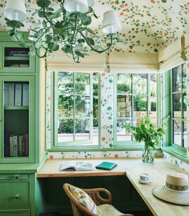 garden office interior with green woodwork, leaf-print wallpaper and floral light fitting