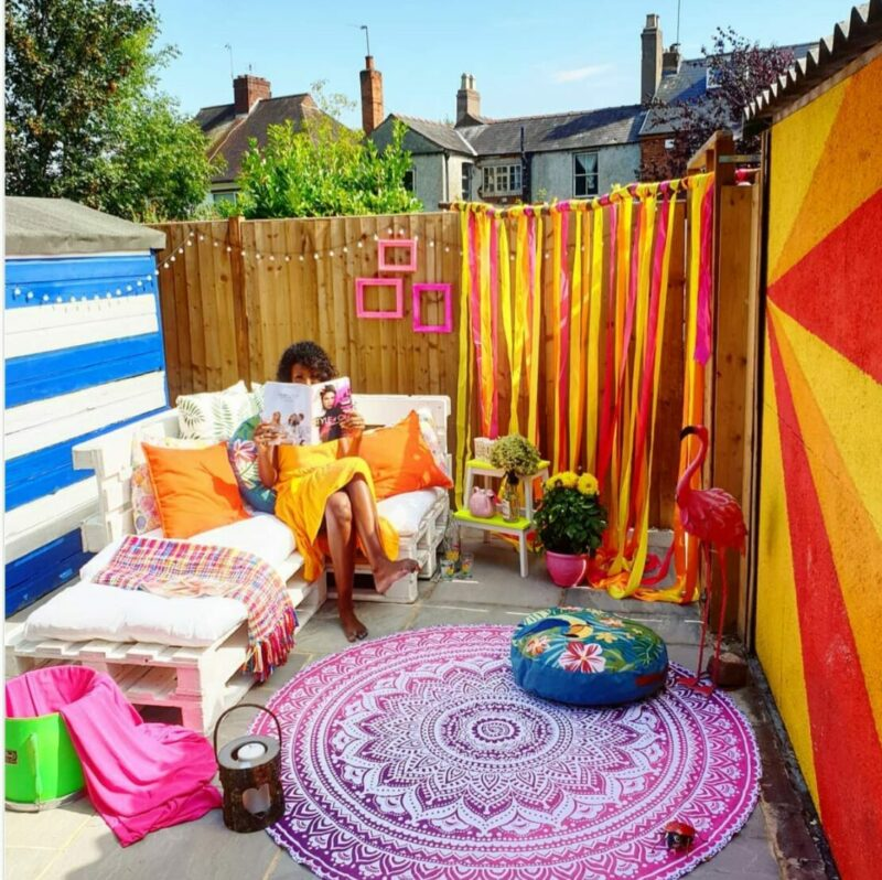 a courtyard decorated with vibrant textiles in a bright, boho style