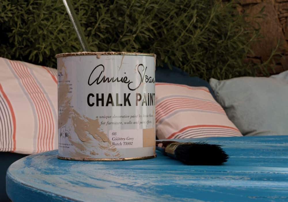 chalk paint on the vintage table next to the paintbrush