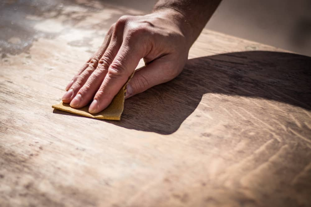 hand sanding a table top to refinish