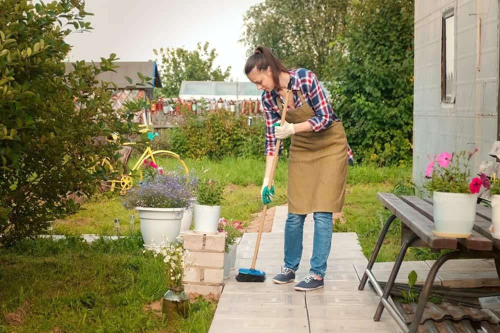 woman gardener sweeping the garden